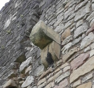 two carved blocks jutting out of the castle wall